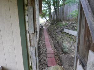 French Drain done! WIth paving stones so wheelbarrows can navigate atop it.